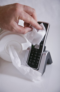 man disinfecting phone