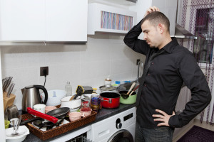 Man facing a cluttered kitchen